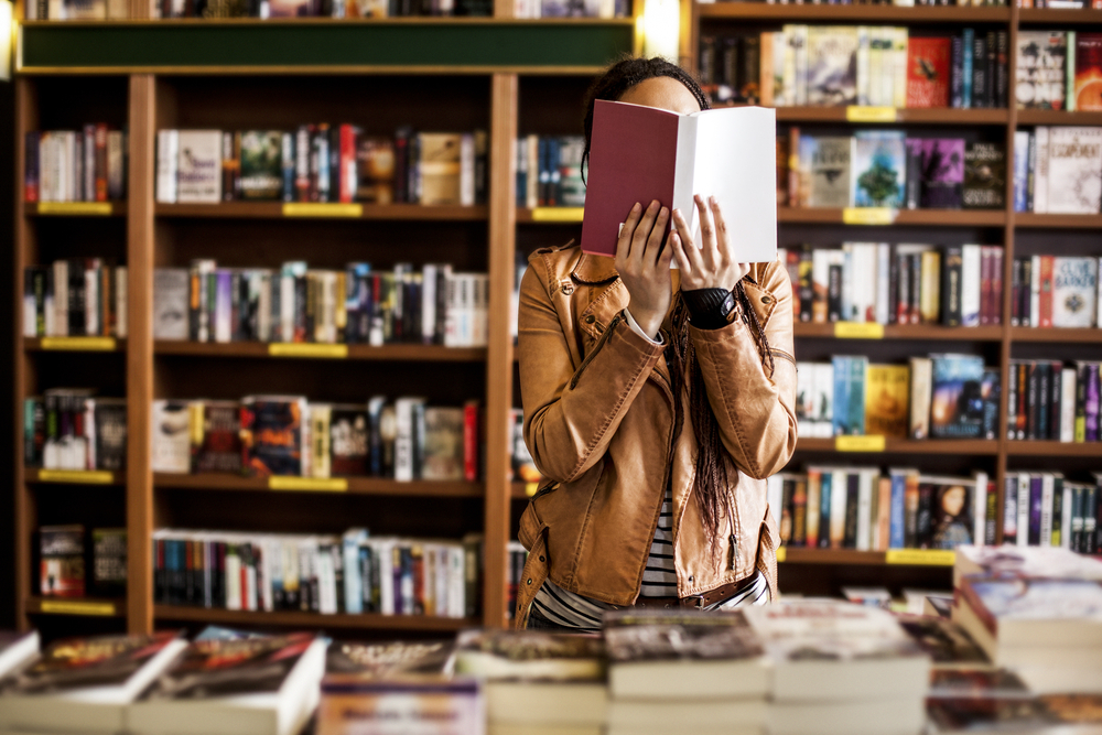 a woman reading a book in a store