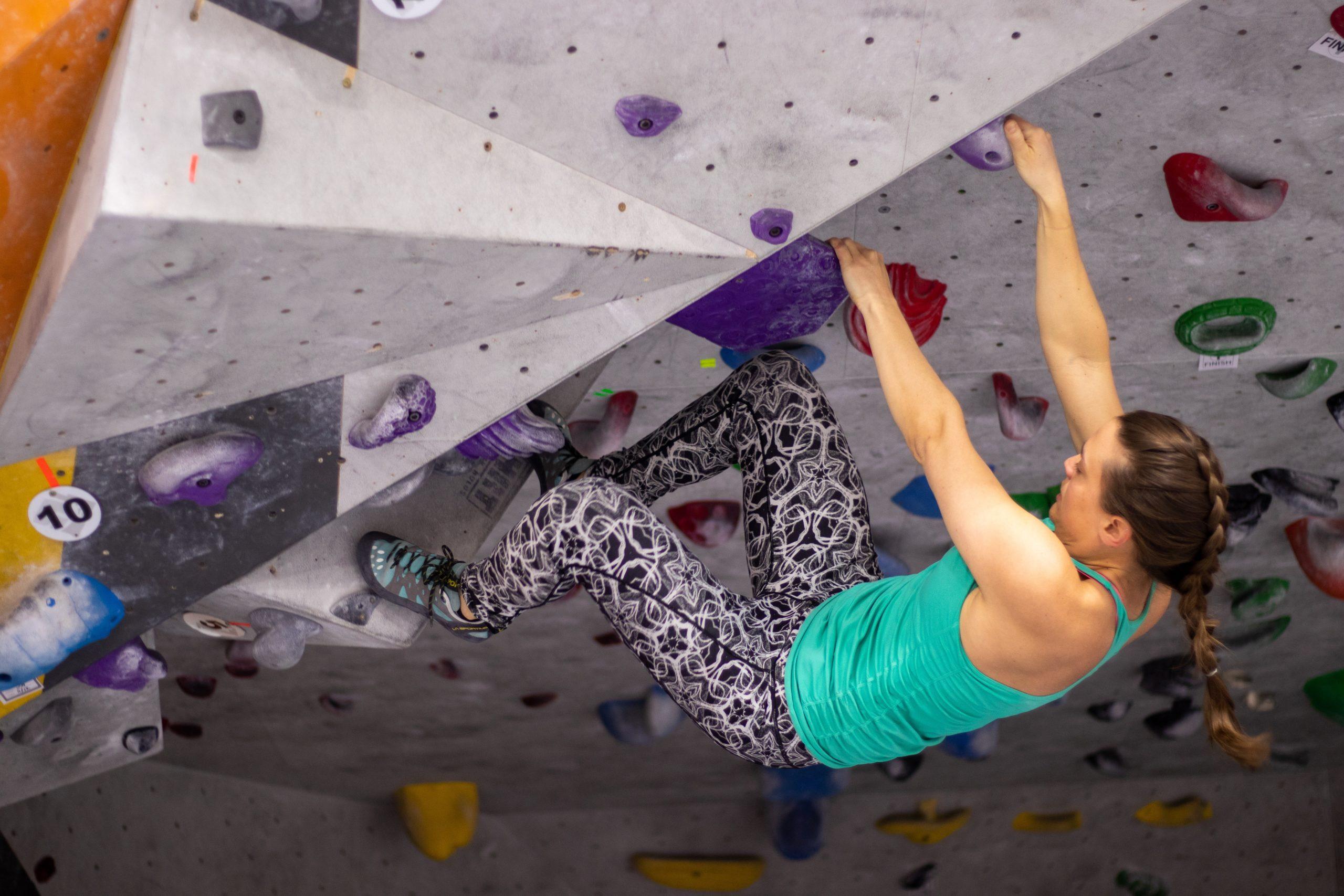 A woman climbs at an indoor rock climbing gym