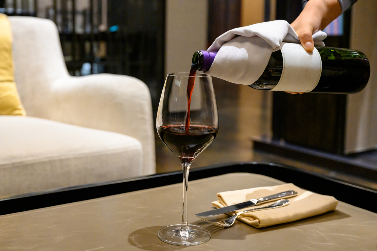 hand pouring red wine at home living room