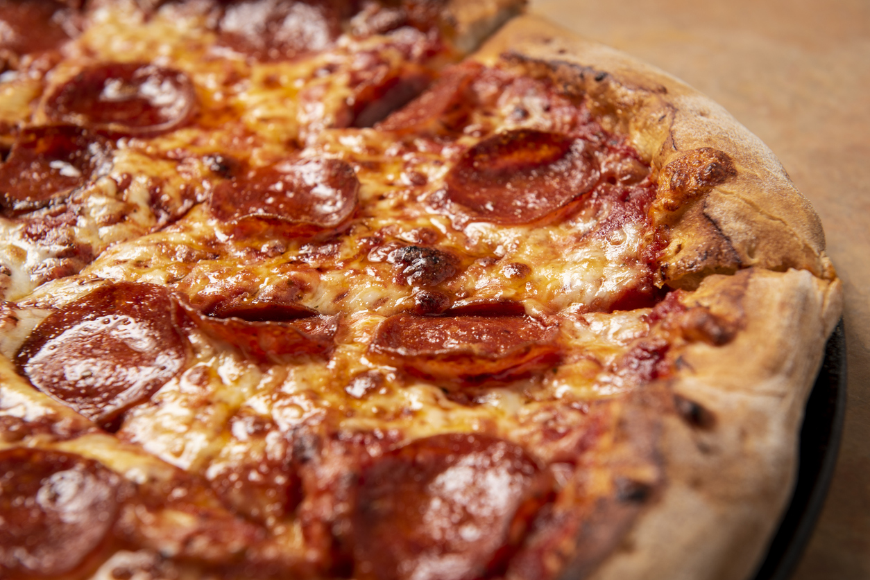 closeup of pepperoni pizza on a wood table