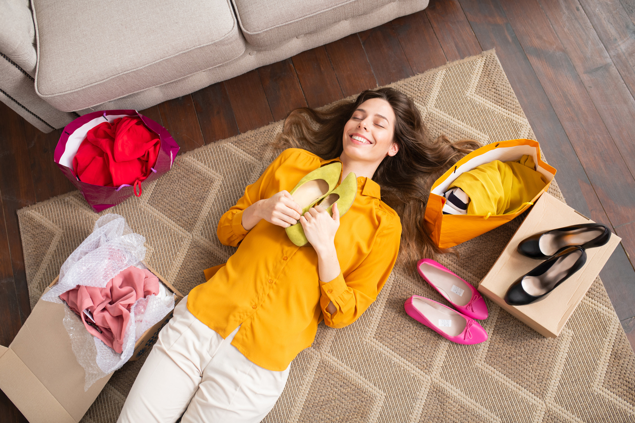 smiling woman holding shoes delivered from clothing stores