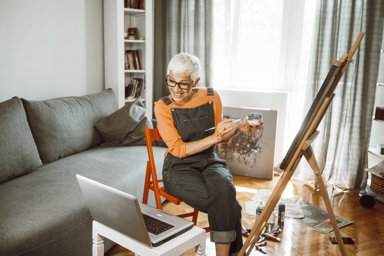 older woman painting at home on her computer