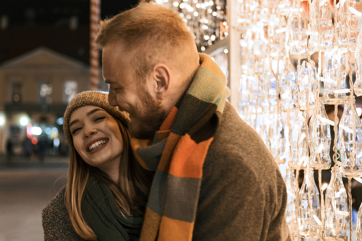 young couple hugging in front of holiday lights