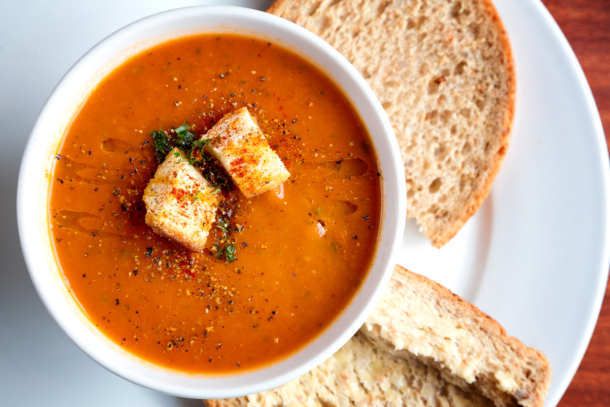 Tomato soup and croutons in a white bowl