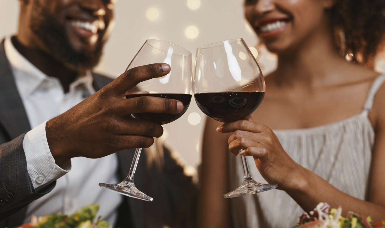 A couple toasting with red wine