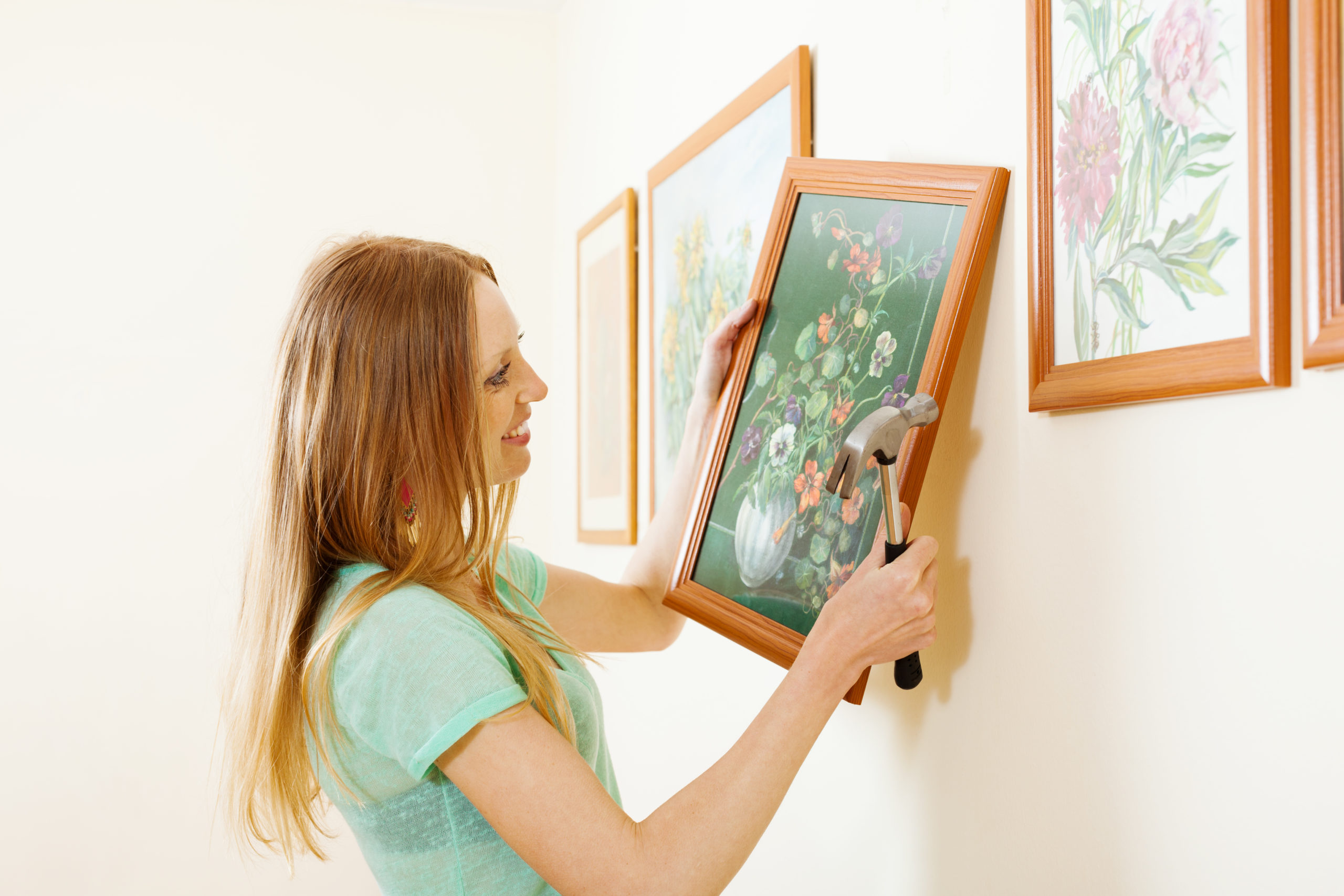 Smiling blonde woman hanging painting with flowers on wall at home